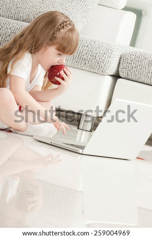 Little Girl Playing with Laptop and Eating an Apple