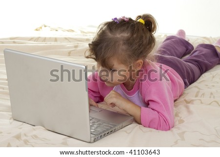 little girl playing with laptop in bad