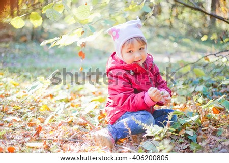 Little girl playing with leaves in an autumn park