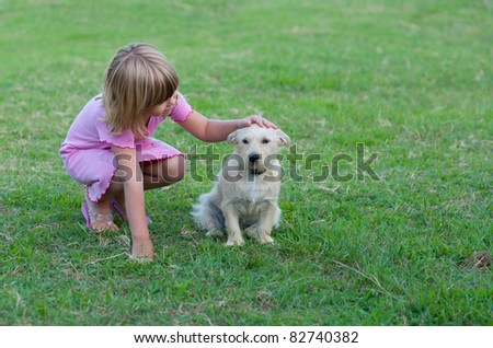 Little girl playing with little white dog. - stock photo