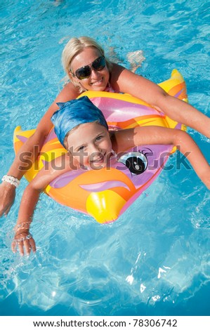 Little girl playing with mother in blue water (no name toy) - stock photo