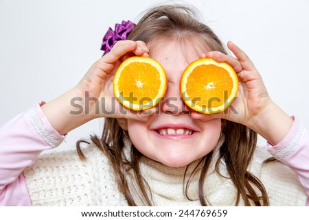 Little girl playing with orange fruits - stock photo