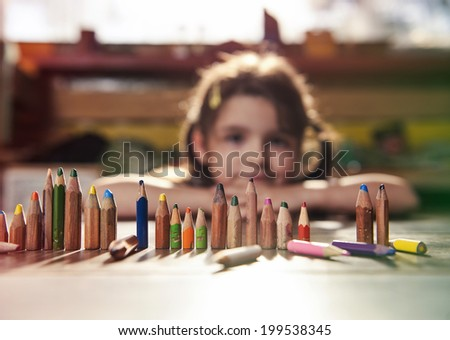 Little girl playing with pencils - stock photo