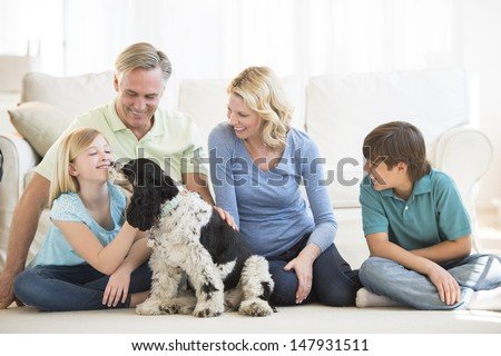 Little girl playing with pet dog while family looking at her in living room - stock photo