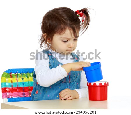 Little girl playing with plastic toys while sitting at table, isolated on white background.