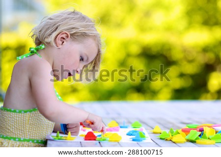 Little girl playing with plasticine and colorful forms. Happy child, adorable toddler girl creating from modeling compound dough, sitting outdoors in the garden on sunny summer day - stock photo