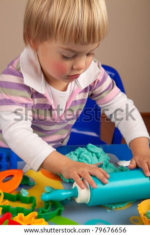 Little girl playing with play-doh - stock photo