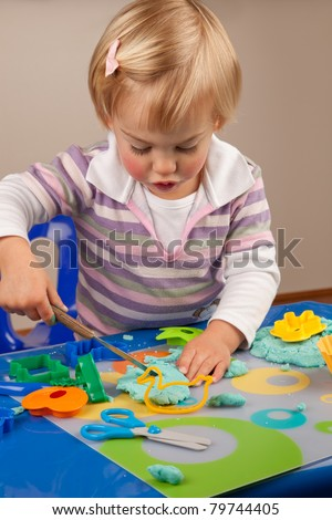 Little girl playing with play dough - stock photo