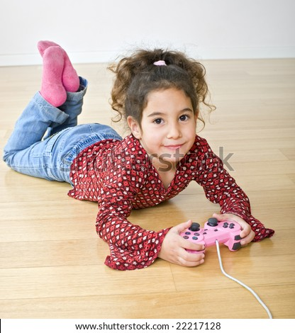 little girl playing with playstation joystick lying on the floor