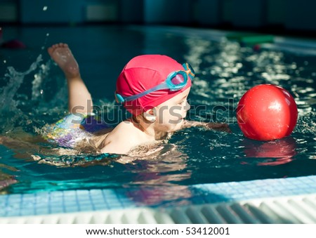 Little girl playing with red ball in a swimming pool - stock photo