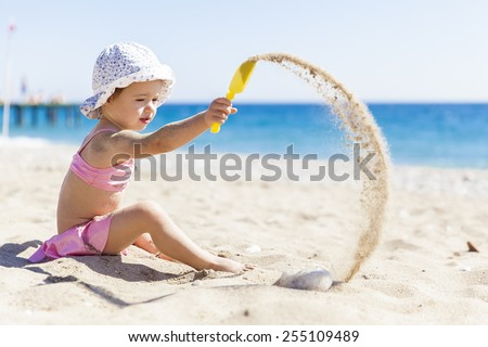 Little girl playing with sand on the beach - stock photo