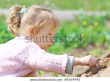 Little girl playing with sand. The child looks very smart and interested.