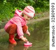 little girl playing with ship in the puddle - stock photo