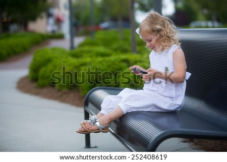 little girl playing with smart phone - stock photo
