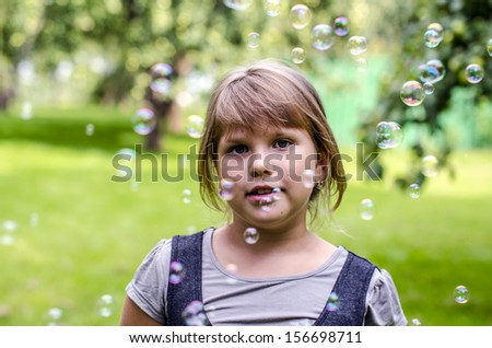 Little girl playing with soap bubbles in summer park