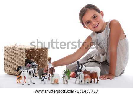 Little girl playing with toy animals - stock photo