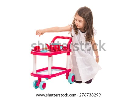 Little girl playing with toy pram with cups isolated on white background - stock photo
