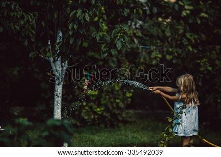 little girl playing with water in the yard