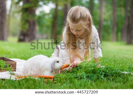 Little girl playing with white rabbit in sunny day outdoor