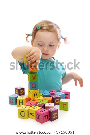 Little girl playing with wooden blocks with letters isolated on white background