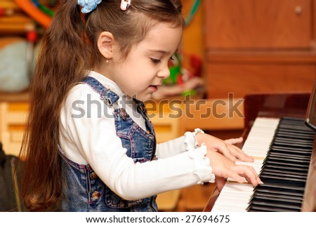 Little girl plays brown piano. - stock photo