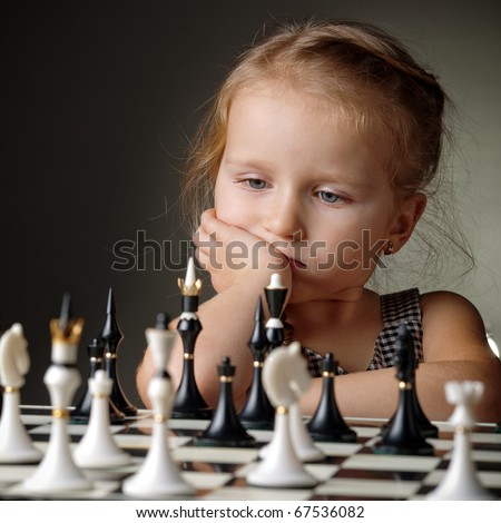 little girl plays chess - stock photo