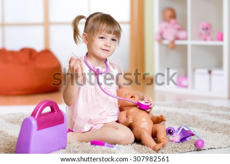 Little girl plays doctor examining baby doll patient with toy stethoscope