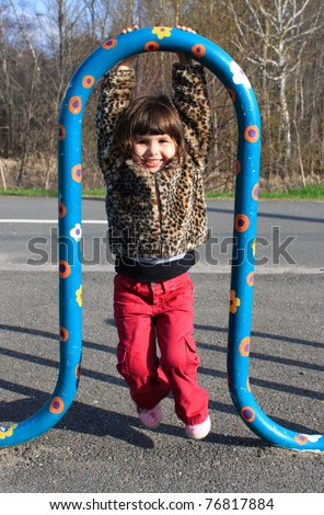 Little girl plays on a colorful bar smiling happily - stock photo