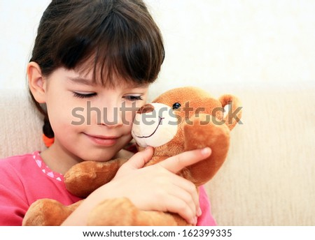 Little girl plays with a brown teddy bear.