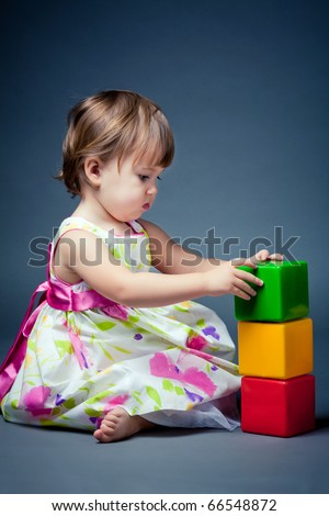 little girl plays with cubes - stock photo