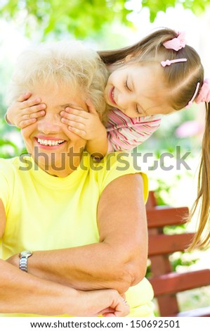 little girl plays with grandmother, closes her eyes outdoors - stock photo