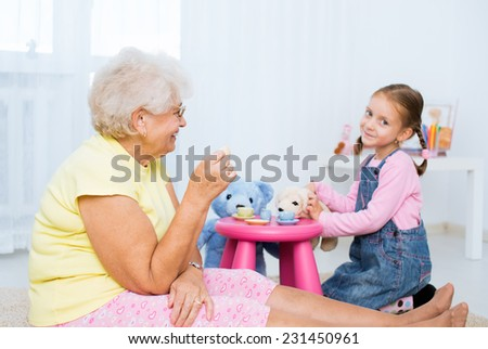 little girl plays with grandmother with her toys - stock photo