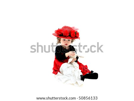 Little girl plays with old fashioned rag doll and wears old fashioned red, straw hat with red silk roses and net.  She is sitting in an all white room and clutching her doll. - stock photo