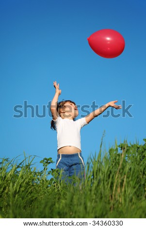 little girl plays with red balloon in grass - stock photo