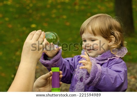 Little girl plays with soap bubbles outdoor on natural autumn background in sunny day - mother hand helps - stock photo