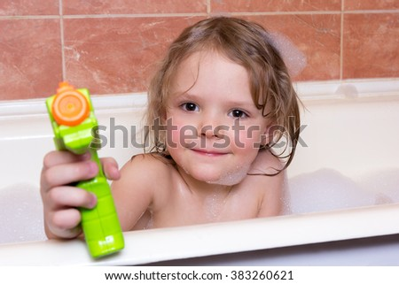 little girl plays with water pistol in a bath with foam