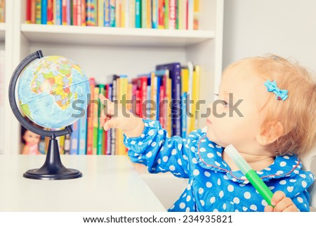 little girl pointing to world globe in classroom, early education - stock photo