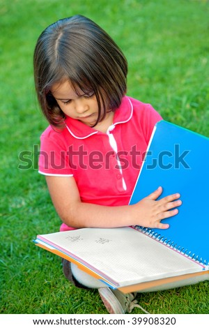 Little girl portrait reading a notebook outdoors