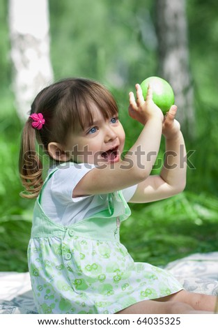 Little girl portrait with green apple in her hands outdoor - stock photo