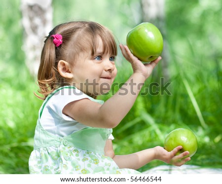 Little girl portrait with 2 green apples in her hands outdoor - stock photo