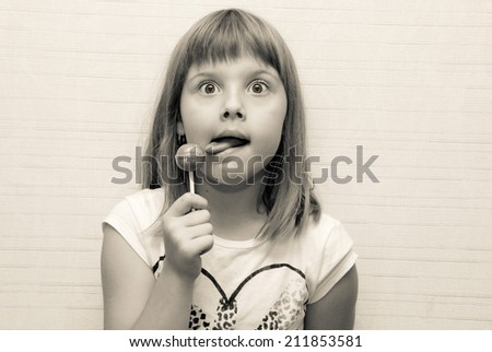 Little girl poses and lick lollypop - stock photo