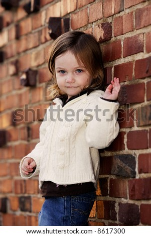 little girl posing in front of brick wall - stock photo