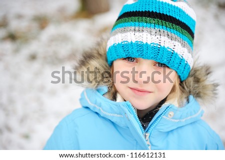 Little girl posing outdoors in winter outfit - stock photo