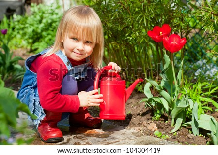 Little girl posing with  red watering can - stock photo
