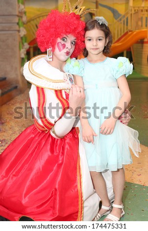 little girl posing with the young actress playing Red Queen closeup - stock photo