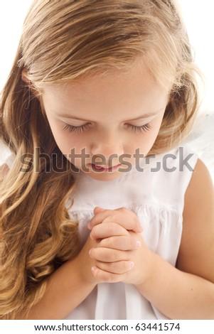 Little girl praying - closeup - stock photo