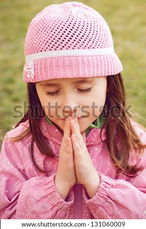 Little girl praying - closeup in the park - stock photo