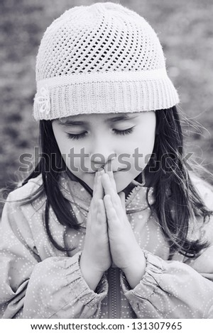 Little girl praying - closeup in the park (in black and white) - stock photo