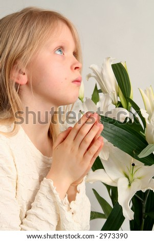 Little girl praying on the easter lilies background - stock photo