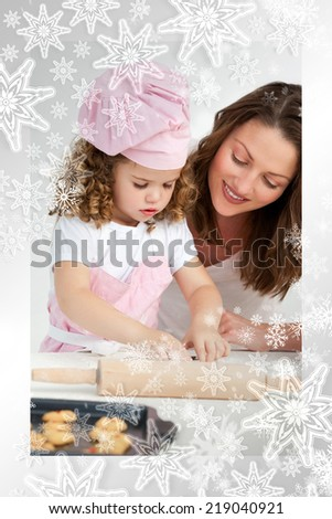 Little girl preparing a daught with her mother against snowflakes on silver - stock photo